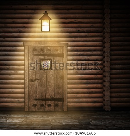 Wooden wall with door and light at night - stock photo