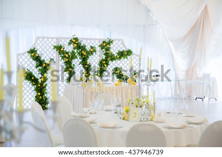 Wooden wall with green garland of lemons stands behind a newlyweds table in white pavilion