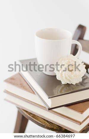 Wooden wall with old chair and books and cup