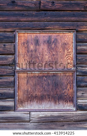 Wooden wall with paint is severely weathered and peeling, old window boarded - stock photo