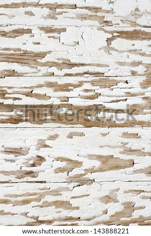 Wooden wall with white paint is severely weathered and peeling - stock photo