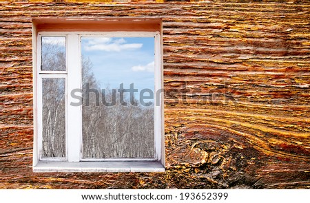 wooden wall with window outside forest clouds