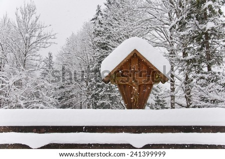 wooden wayside cross covered with snow