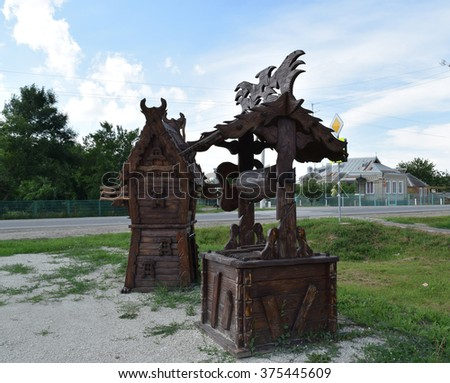 Wooden well and a windmill. Wooden decorations.