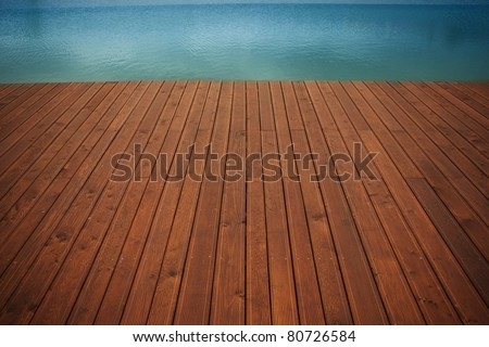 Wooden wharf and blue water - stock photo