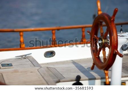 Wooden wheel on luxury yacht - stock photo