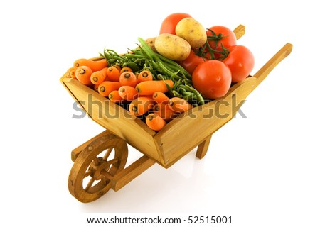 wooden wheelbarrow full with fresh vegetables isolated over white - stock photo