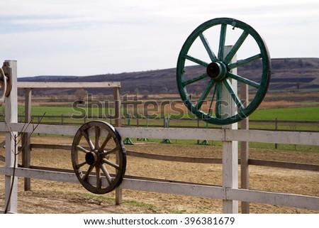 Wooden wheels of old carts hung on a wall. - stock photo