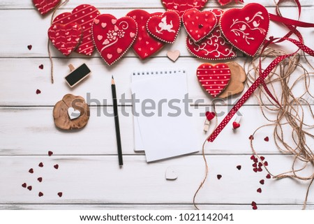 Wooden white background with Red heart shaped cookies with different patterns, Love letter with pencil, gifts. The concept of Valentine Day