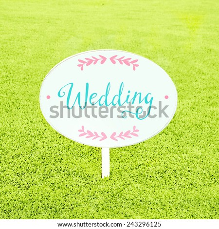Wooden white blank sign on grass - stock photo
