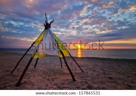 Wooden wigwam on the shore of the ocean - a colorful sunrise and beautiful clouds - stock photo