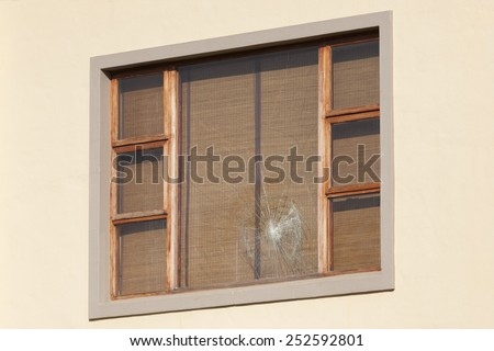 Wooden window frame with one shattered window pane - stock photo