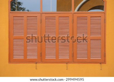 Wooden window shutter of an orange house