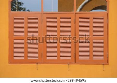 Wooden window shutter of an orange house - stock photo