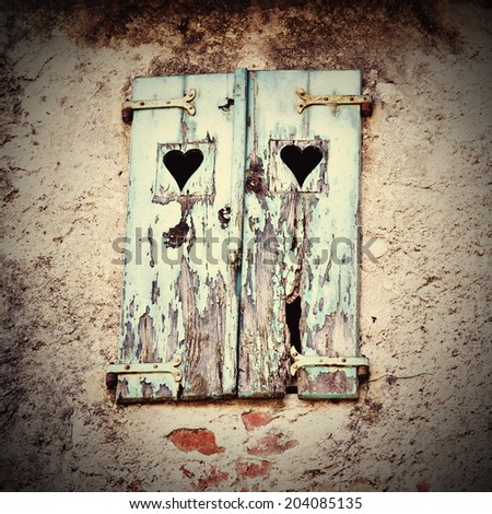 Wooden window shutters with heart shape - Closed old shuttered weathered wooden window in Italy - stock photo