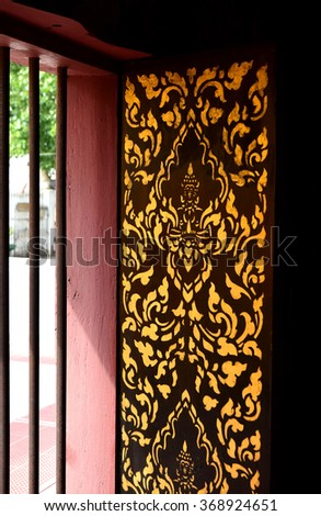 Wooden window with carved and gilded of Thai Buddhist temple - stock photo
