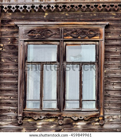 Wooden windows lacy architecture of old wooden houses in Tomsk, Siberia. Carved decoration of natural colors, wooden window of an old building. Dual window.