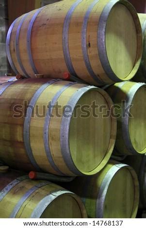 Wooden wine barrels waiting for bottling - stock photo