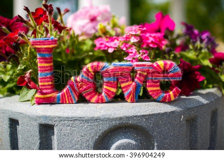 Wooden word love. Colored thread. Wooden letters forming word love - stock photo