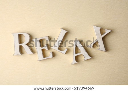 Wooden word RELAX on light background
