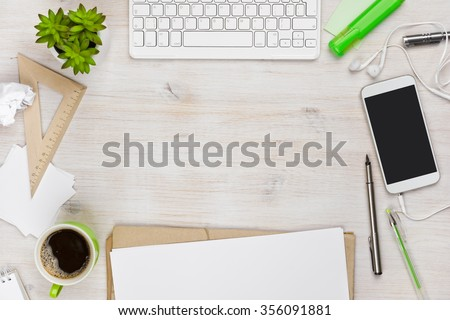 Wooden work desk top view with copyspace in the middle - stock photo