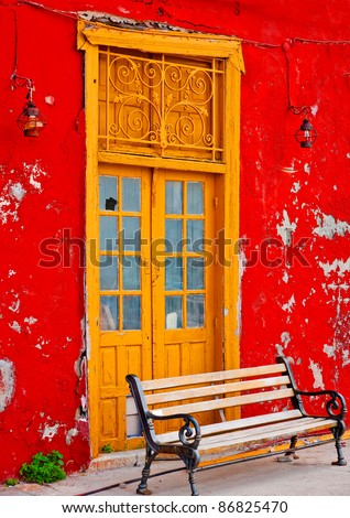 Wooden yellow beautiful door in an old red colored building in the small port Kamini of Hydra island in Saronikos gulf in Greece - stock photo