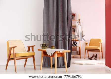 Wooden yellow chair next to a table with kettle in dining room interior with walk-in wardrobe behind grey cloth