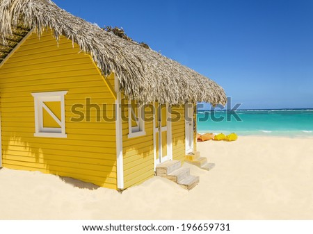 Wooden yellow hut on the beach covered with thatch against colorful kayaks, blue sky and azure water, Caribbean Islands  - stock photo