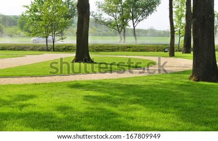Woodland park with lush green neat manicured lawns and a road or walkway meandering through between the tree trunks, scenic background view - stock photo