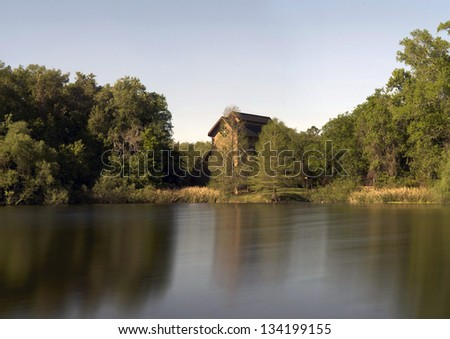 Woods, a chapel, and a lake. - stock photo
