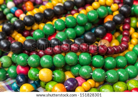 Woods multi colored beads heap. A bead is a decorative object that is usually pierced for threading or stringing.  - stock photo