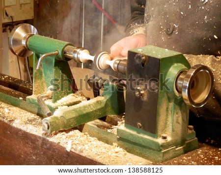 Woodturner creating a spinning top on a lathe - stock photo