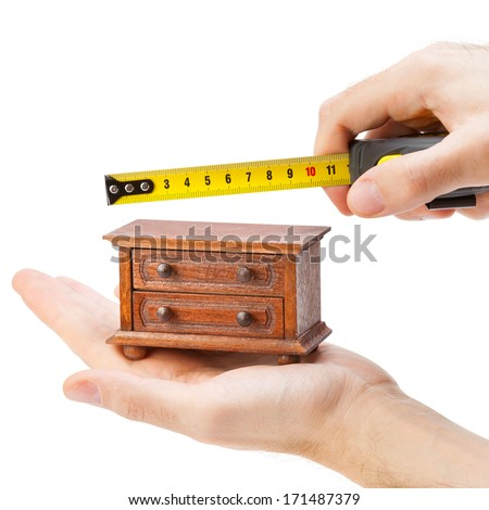 woodworker measuring chest of drawers with a tape measure, carpentry concept - stock photo