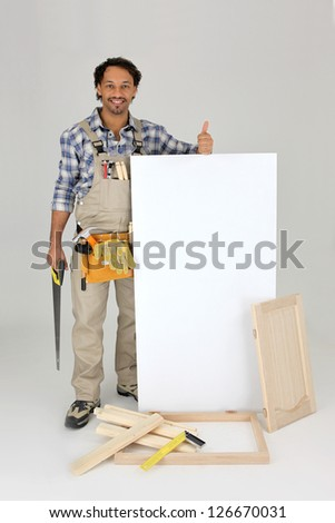 Woodworker stood with cabinet door and advertising panel - stock photo