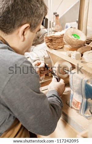 Woodworker working on grinder finishing smoking pipe - stock photo