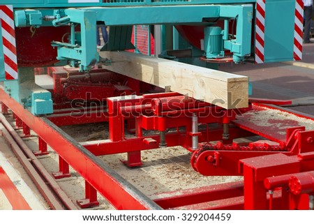 Woodworking the Machine Tool, Wood factory Outdoors, Close-up. Steel Band saw Machine working in Factory. Wood Shavings, planks - stock photo
