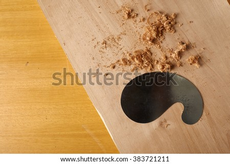 Woodworking tool. Shavings with card scraper blade on a workbench. - stock photo