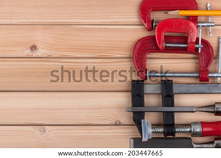 Woodworking tools and a pencil on a wooden background. - stock photo