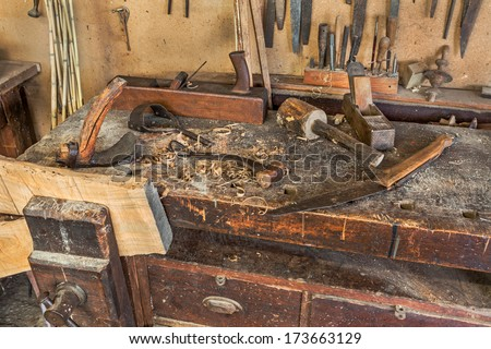 woodworking tools of antique carpentry - old bench with carpenter's equipment  - ancient carpentry craftsman workshop   - stock photo
