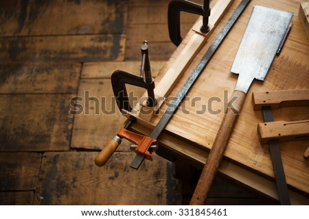 Woodworking. Wood working project on work bench, in a workshop with wooden floor. Clamped pieces of wood with c-clamps and bar clamp. shot in low key and shallow depth of field.   - stock photo