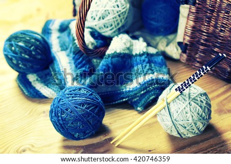wool balls and knitting needles on a wood background - stock photo