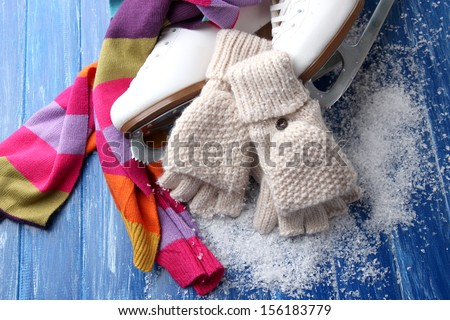 Wool fingerless gloves and skates for figure skating, on wooden background - stock photo