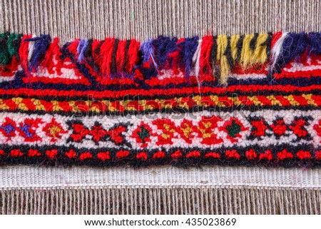 wool handmade carpet. Partly woven carpet, rug on a loom shows wool pile, foundation, warp and weft. Wool is dyed with natural vegetable dyes to create vibrant look. - stock photo