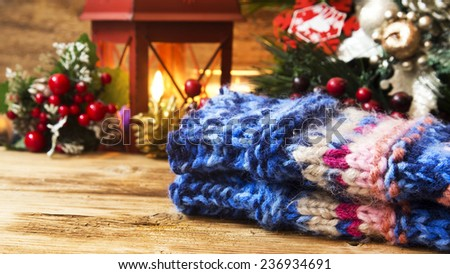 Wool Handwarmers with Christmas Decorations and Lantern Light in the Background - stock photo