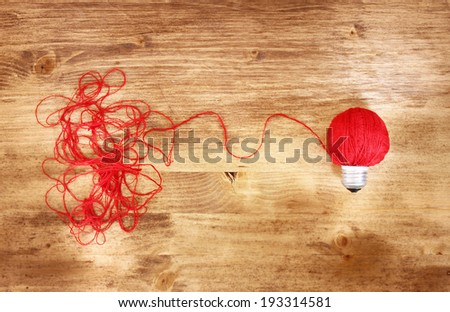 wool light bulb . idea or inspiration concept on wooden background  - stock photo