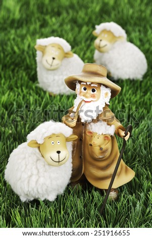 Wool sheep figurines and shepherd on grass - stock photo