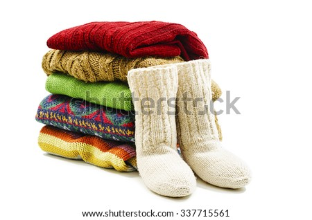 Wool socks and stack of various sweaters. Winter style. Isolated on white background - stock photo