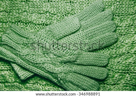 Wool sweater or scarf and gloves texture close up. Knitted jersey background with a relief pattern. Braids in machine knitting pattern. Wool hand-knitted or machine knitting pattern. Fabric Background - stock photo