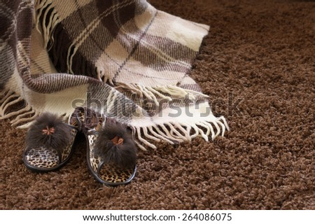 Woolen checked plaid and slippers on shaggy carpet. - stock photo