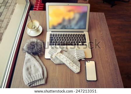 Woolen hat with pompon and mitten near a laptop and cup of coffee on the wooden table - stock photo
